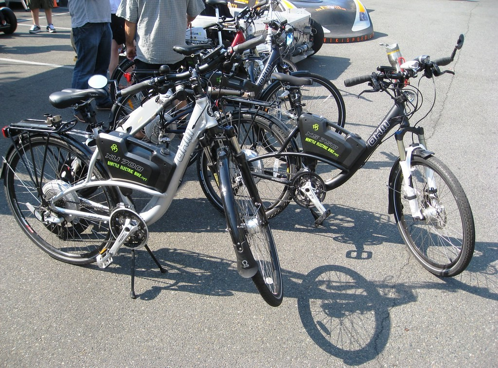 Several electric bicycles parked on a road top.